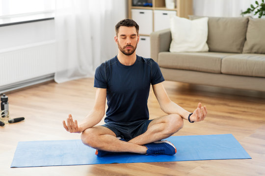 sport, fitness and healthy lifestyle concept - man meditating in lotus pose on yoga mat at home