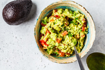 Fresh avocado tomato guacamole in a bowl. Healthy plant based food concept. Wall mural