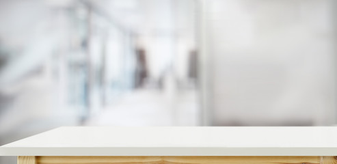Wall Mural - White wood top table over office blurred background