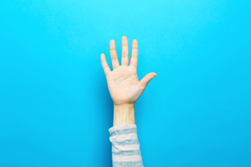 Person raising their hand up on a blue background