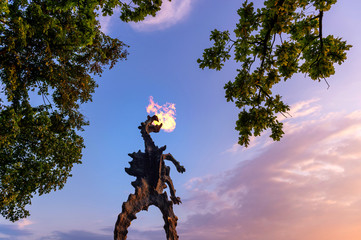 Symbol of Cracow - legendary polish wawel fire breathing dragon monument against blue sky at sunset.