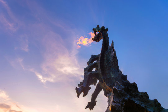 Symbol of Cracow - legendary polish wawel dragon monument with fire coming out from its mouth against blue sky at sunset.