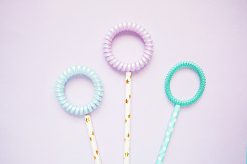 flat lay flowers of spiral hair bands and tubes on a pink background copy space, abstract background.