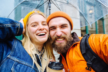 "Hipster couple traveler under transparent umbrella making selfie photo saluting you, saying ""Hi"" in city street Positive beard man and blonde woman drrinking hot coffee.. Lifestyle love concept."