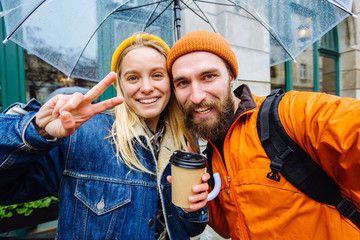 Self-portrait of nice cute lovely attractive magnificent blond girl with wavy hair in casual denim jacket,, showing v-sign near eye and her beard handsome boyfriend in orange hat and jacket outdoor.
