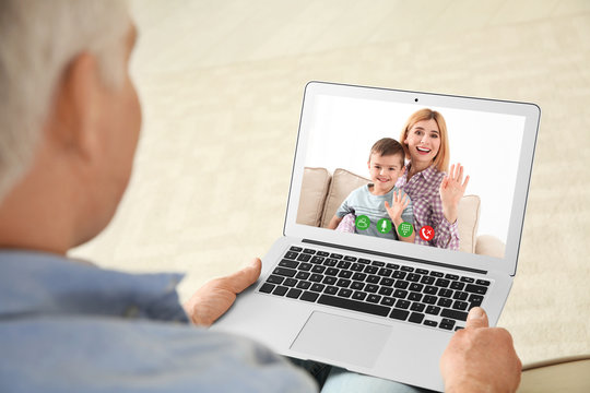 Closeup view of senior man talking with family members via video chat at home