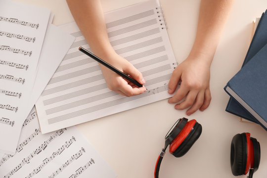 Child writing music notes at table, top view