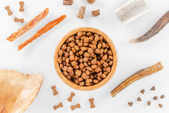 different dog food and snack, chicken filet, antlers, lung, ear on white background, top view