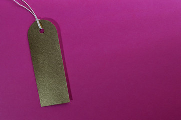 gold curved rectangle paper tag on pink background