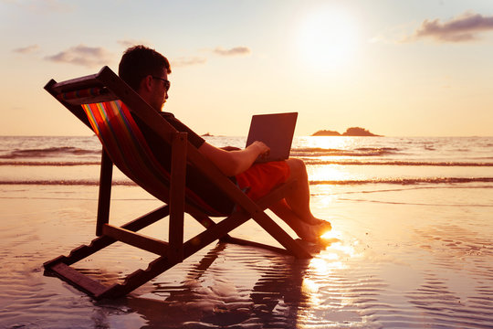 freelancer business man working on computer in beach office at sunset, freelance work, silhouette of happy person typing on laptop