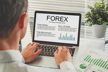 Forex concept on the screen of computer, business man reading about trading