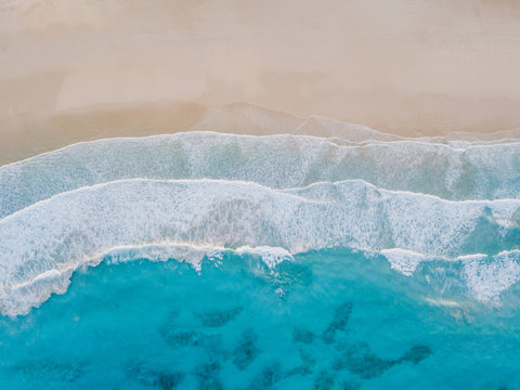 Aerial view of sand beach, ocean texture background looping, top down view of sea waves by drone.