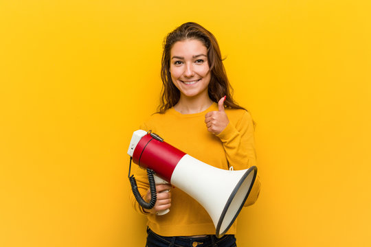 Young european woman holding a megaphone smiling and raising thumb up