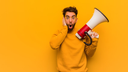 Young man holding a megaphone surprised and shocked