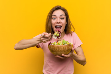 Vegan young woman eating a fresh and delicious salad.