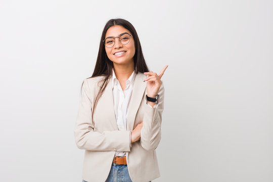 Young business arab woman isolated against a white background smiling cheerfully pointing with forefinger away.