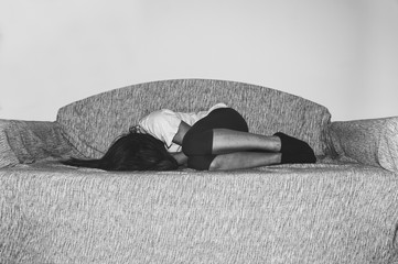 Depressed and lonely girl abused as young lies alone in her room on the bed feeling miserable and anxiety cry over her life, dark image black and white hard contrast