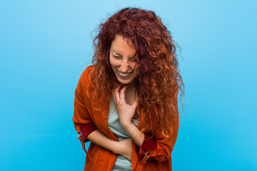 Young redhead elegant woman laughs happily and has fun keeping hands on stomach.