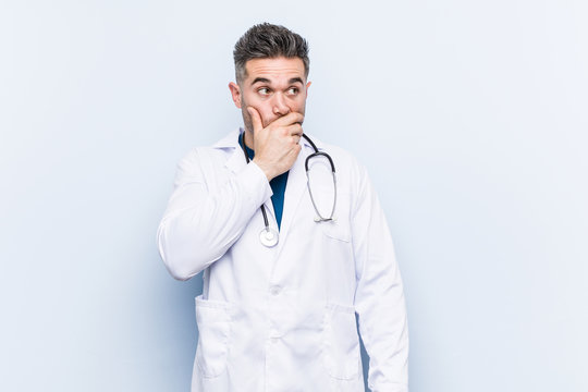 Young handsome doctor man thoughtful looking to a copy space covering mouth with hand.