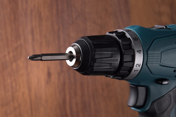 rechargeable electric screwdriver on wooden background. Repair and handicraft.