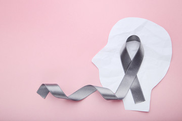 Grey ribbon and head shape from paper on pink background. Brain cancer concept