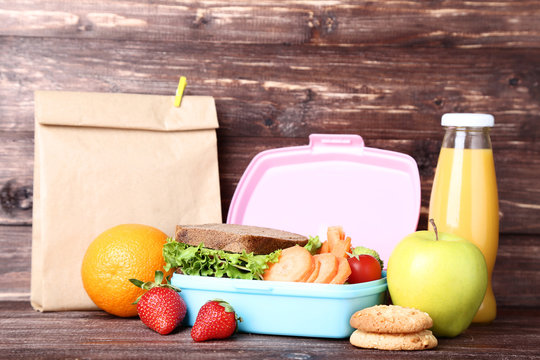 School lunch box with sandwich and fruits on wooden table