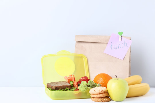 School lunch with paper bag on grey background