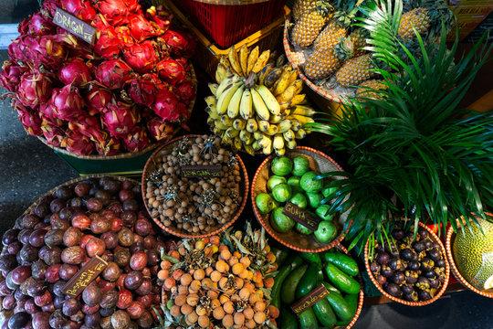 Exotic and tropical fruits on the market of Asia, Thailand, Vietnam. Mini bananas, longan, pitaya (Dragon Fruit), papaya.