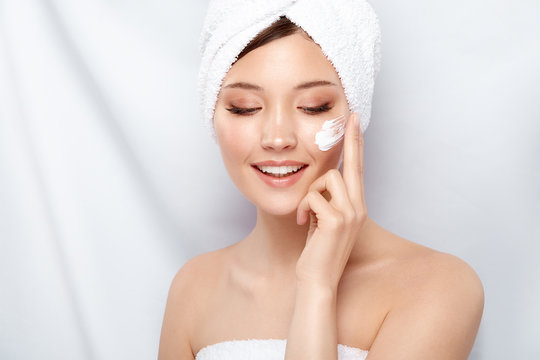 pretty girl with bath towel smilling and putting on facial cream on cheek, happy face care, body treatment, beauty concept