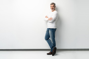 Full body portrait of relaxed mature man standing with arms crossed over white background. Wall mural