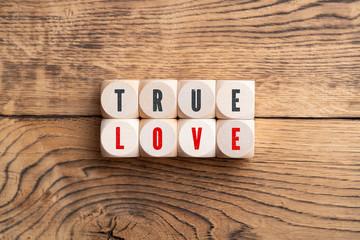 """Würfel mit Aufschrift """"TRUE LOVE"""" auf Holzuntergrund"""