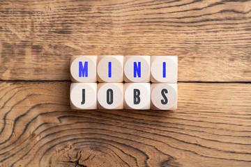 """Würfel mit Aufschrift """"Mini Jobs"""" auf Holzhintergrund"""