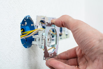 Hands of electrician installing electrical socket with new home