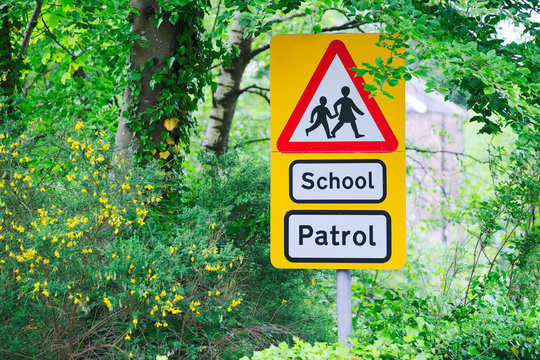School patrol yellow and red triangle sign near entrance