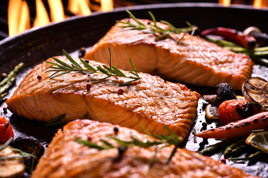 Grilled salmon fish with various vegetables on pan on the flaming grill