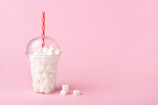 Shake Glass with straw full of sugar cubes on pink background Unhealthy diet concept