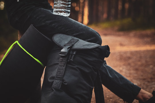 A person in dark denim is relaxing in the forest sitting on rolled mat and backpack.