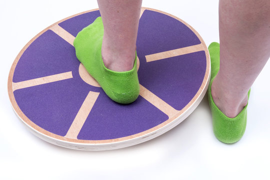 Woman's foot on Wooden Wobble Balance Board Exercise Core Fitness Trainer for Workout, Fitness, Balance Exercise & Rehabilitation.