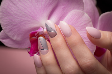 Poster de jardin Manicure Purple neat manicure on female hands on flowers background. Nail design