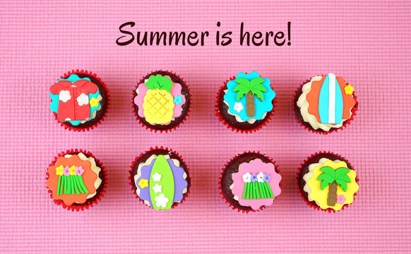 Summertime flat lay concept with tropical vacation theme cupcakes on pink background.