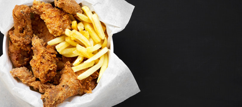 Tasty fastfood: fried chicken legs, spicy wings, French fries and chicken stips in paper box over black background, top view. Flat lay, overhead, from above. Copy space.