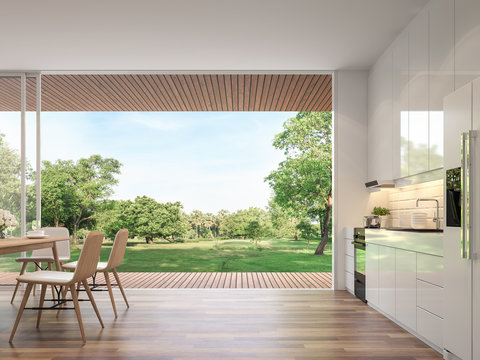 Modern dining room 3d render.Rooms have wooden floors, decorated with wooden furniture and a glossy white kitchen counter with large open doors. Overlooking the terrace and large garden.
