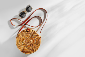 Wall Mural - Fashion round bamboo bag and sunglass. Flat lay, top view. Spring/summer fashion concept.