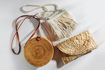 Wall Mural - Variety summer handbags on white background. Round bamboo bag, handbag with fringe and straw bag. Flat lay, top view. Fashion concept.