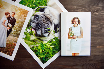 Photo canvas prints. Sample of stretched photography of woman with gallery wrap. Printed photos of a dog and a wedding couple lying on a wooden  table. Top view