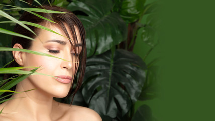 Beautiful woman surrounded by green plants. Organic cosmetics and body care concept