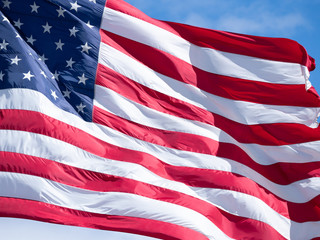 Extreme Close Up of an American Flag with Blue Sky and Thin Clouds in Background