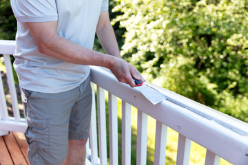 Close up of mature man scraping old paint from outdoor deck