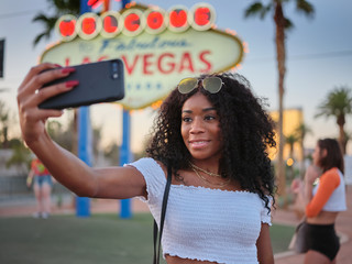 african american woman taking selfie with smartphone in front of welcome to las vegas sign