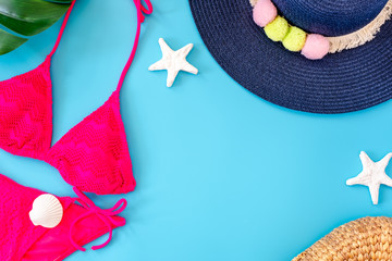 Wall Mural - summer blue banner with navy blue hat ,pink bikini,sunglasses and seashell on blue background top view.